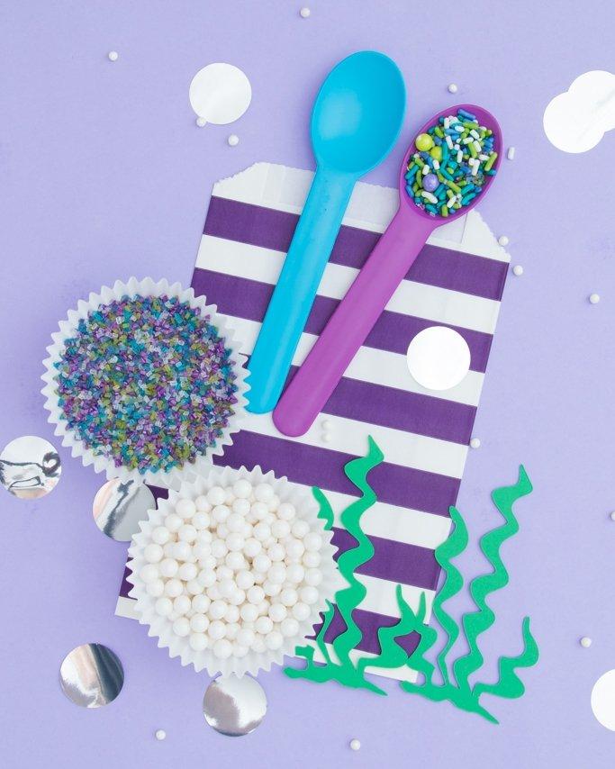 Mermaid party ideas - Mermaid sprinkles on purple stripe goodie bag and seaweek cutout confetti.
