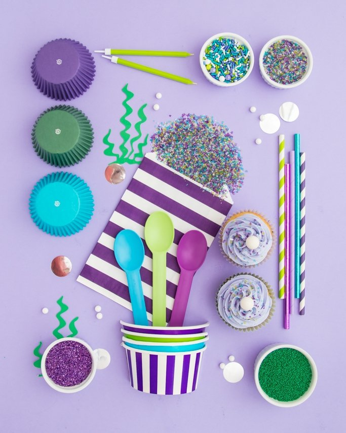 Mermaid party supplies on a purple background with seaweed cutout mermaid party ideas.