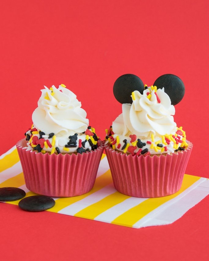 Mickey Mouse Cupcakes with black ears and Mickey sprinkles on red background
