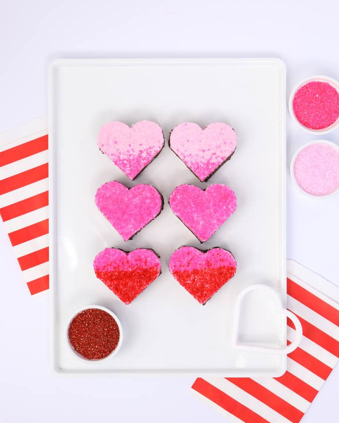 ombre heart shaped valentine brownies on white plate topped with pink and red sugar crystals
