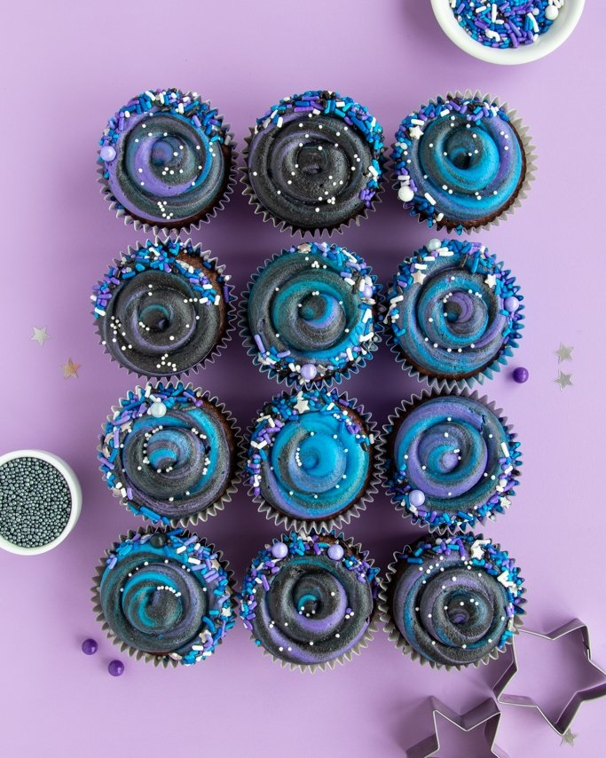 Swirly Galaxy Cupcakes in grid layout on purple background rolled in Outer Space sprinkles