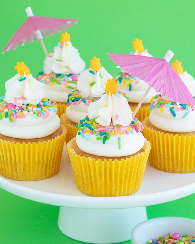Pina Colada Cupcakes with paper umbrellas on white cake stand