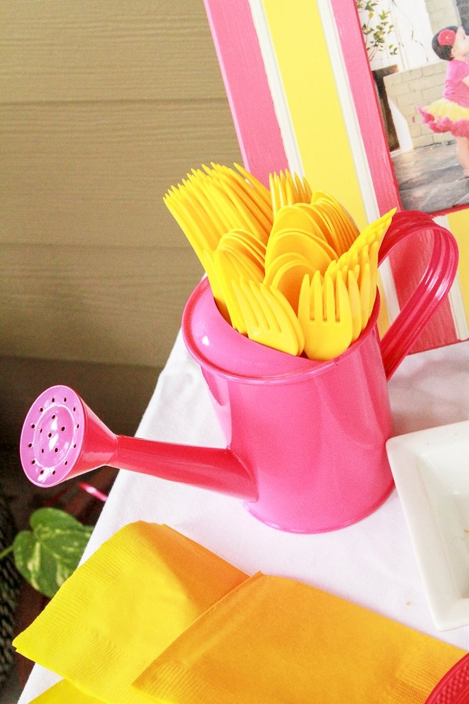 Pink watering can filled with plastic silverware