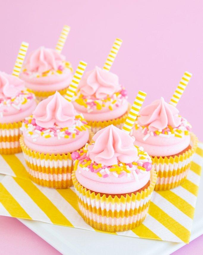 Half dozen pink lemonade cupcakes on white dish
