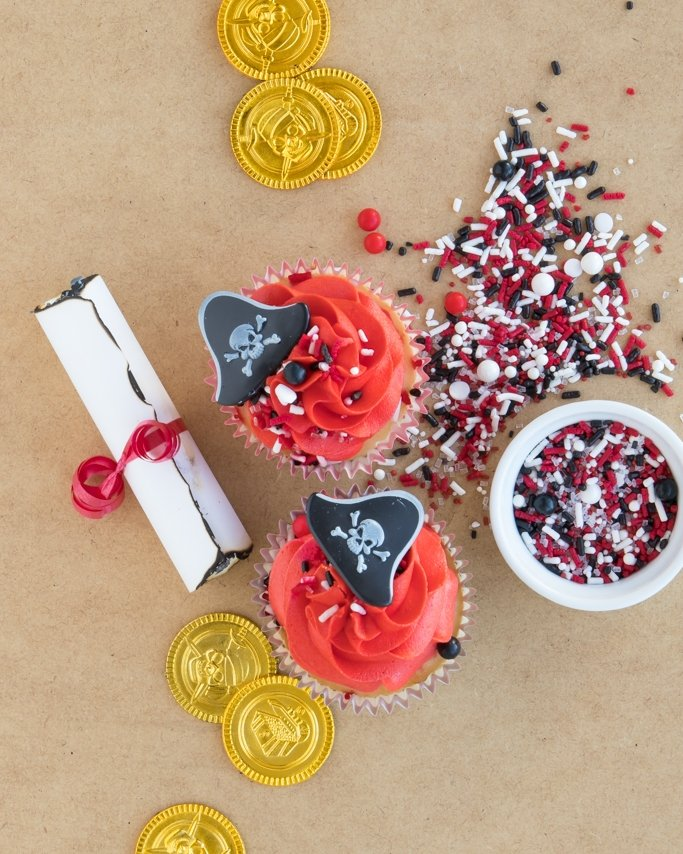 Pirate Party Cupcakes and sprinkles with gold coins and letter scrolls on tan background