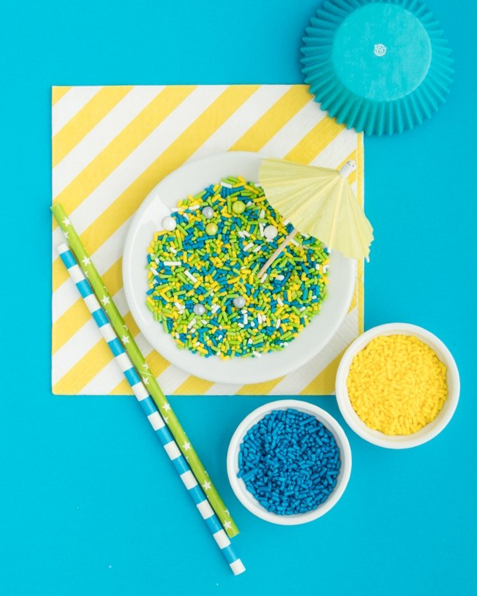 Pool Party Ideas - Sprinkles in white dish with pool party supplies all around on blue background