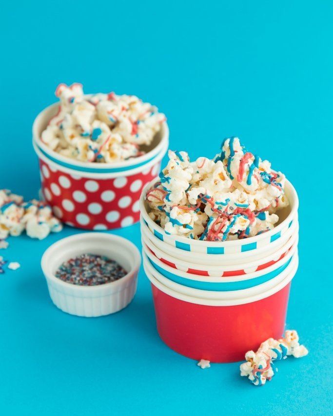Patriotic Popcorn - Easy 4th Of July Snack in red, white, and blue ice cream cups on blue background