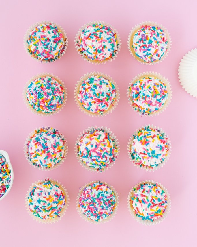 Full coverage dipped sprinkle cupcakes with rainbow sprinkles on top