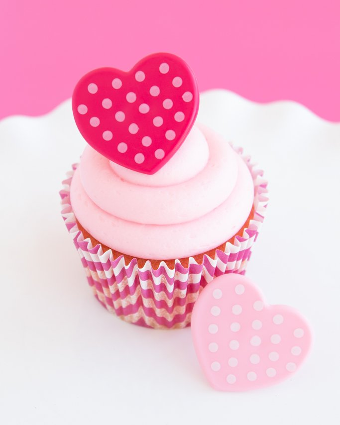 closeup of strawberry cream cheese cupcakes with pink heart ring topper on top