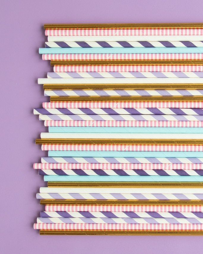 Sugar Plum Fairy Party Paper Straws in assorted colors on light purple background