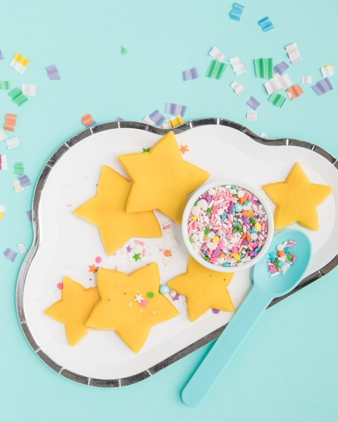 Yellow Star Cut Out Cookies - Pajama Party Ideas on cloud plate and cupcake liner confetti on blue background