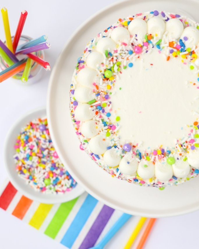 Top of rainbow sprinkle cake with napkin and sprinkles underneath