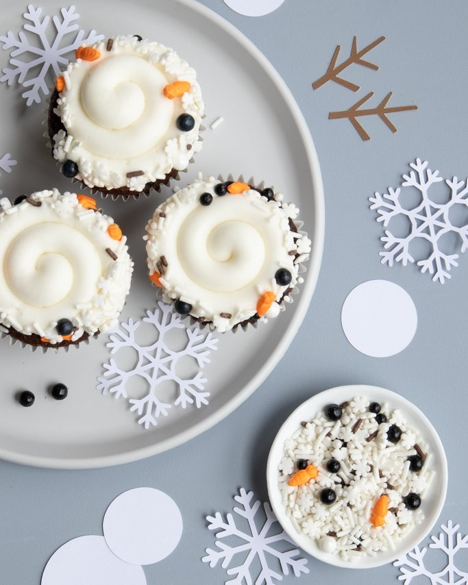 top view of melted snowman cupcakes and snowflake paper table confetti