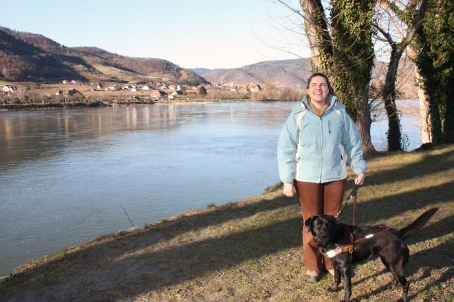 Núria y Bella y de fondo río, montañas verdes y un pueblecito austríaco.