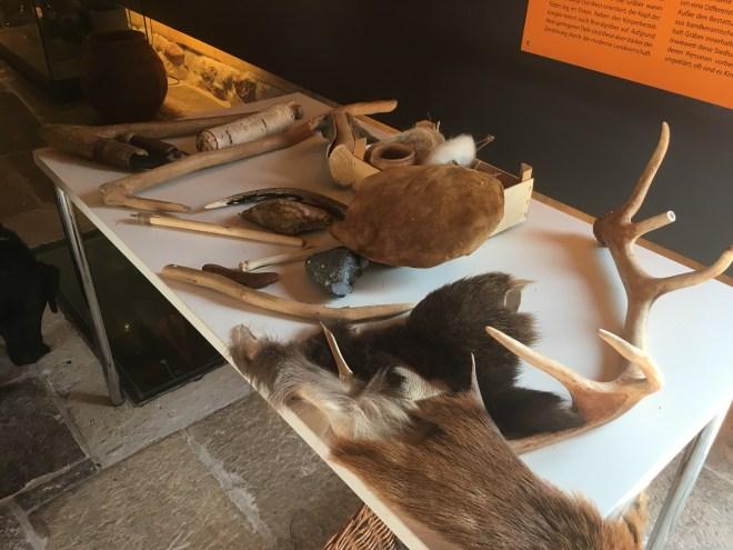 Mesa repleta de réplicas de herramientas y objetos prehistóricos