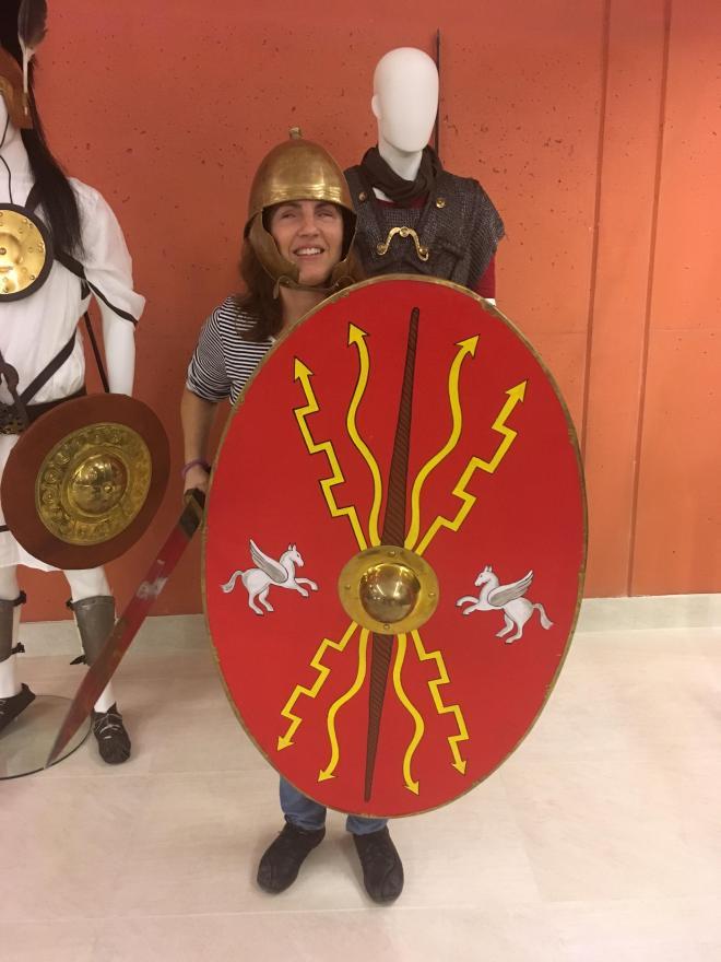 Núria en vilamuseu equipada con casco, escudo y espada romanos.