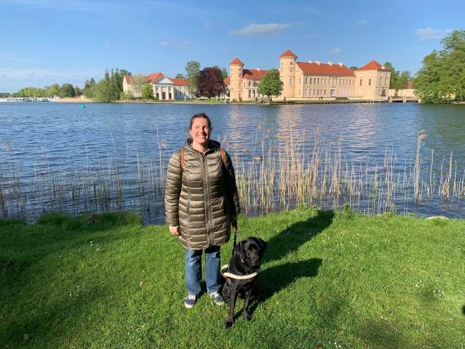 núria con su perro guía a la orilla del lago grienerick y de fondo el palacio Rheinsberg