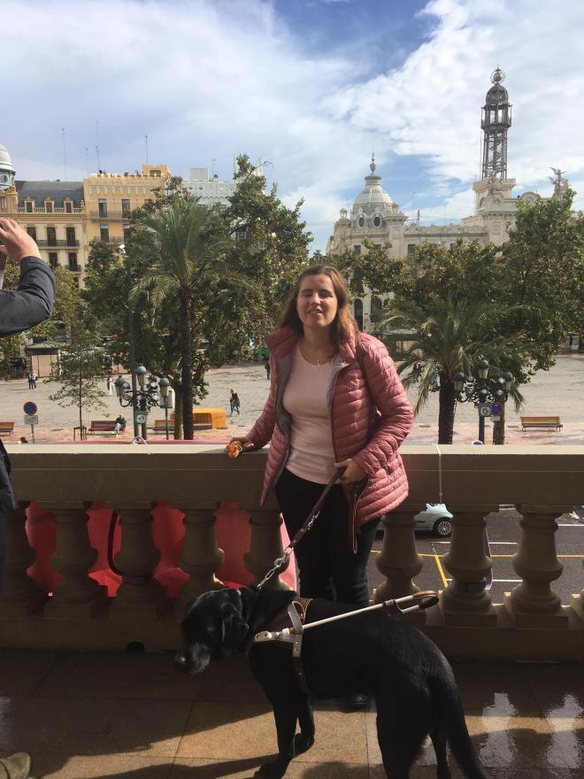 Núria con su perro guía y su caracol viajero en el balcón del ayuntamiento de Valencia con vistas a la plaza.
