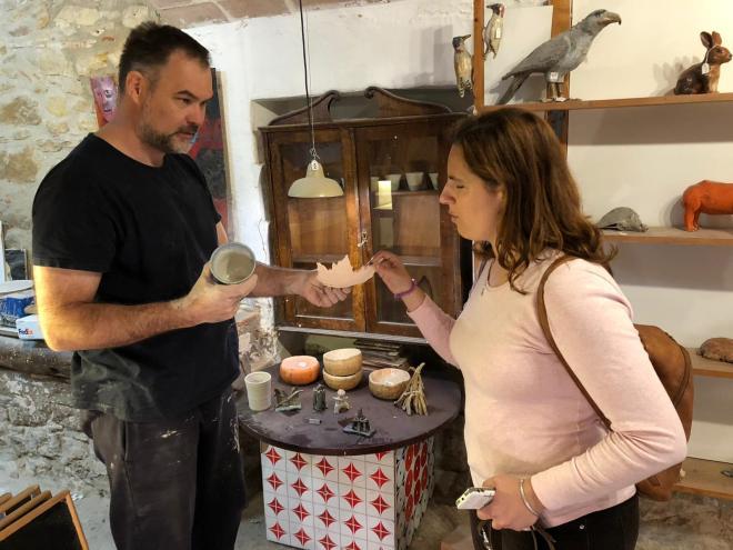Núria y Oldo en el taller del ceramista, él enseña sus piezas a Núria para que las toque.