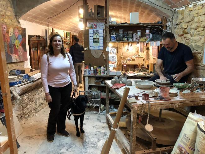 Núria y su perro guía en el taller del ceramista. Se ve al ceramista trabajando con su torno y el taller con piezas en las paredes, se ve un taller antiguo.