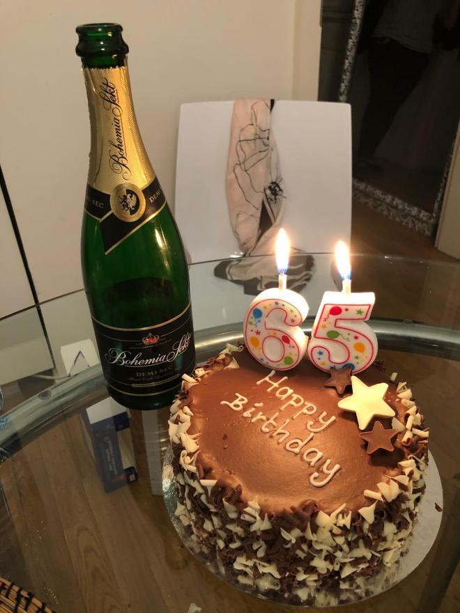Foto tipo bodegón con botella de cava, pastel y velas en el apartamento de Praga