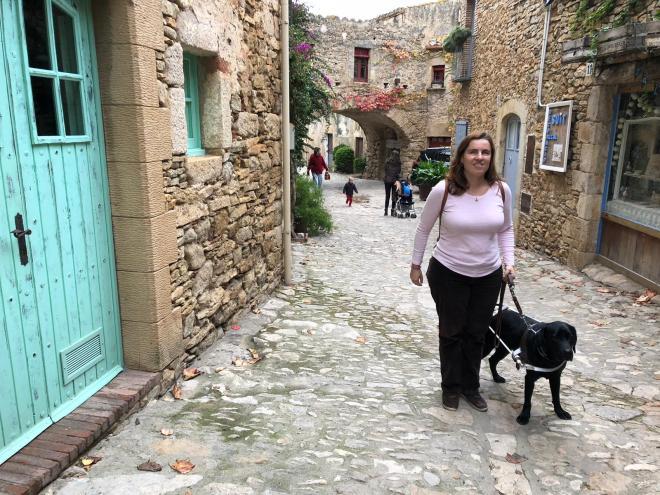 Núria y su perro guía en una calle empedrada en Peratallada. Se ve un pueblo muy antiguo, medieval con las casas tambiénb de piedra.