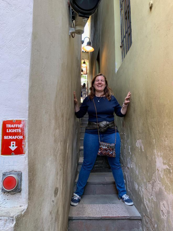 Núria en la calle más estrecha del mundo, abriendo brazos y piernas que llegan a ambas paredes y riendo.