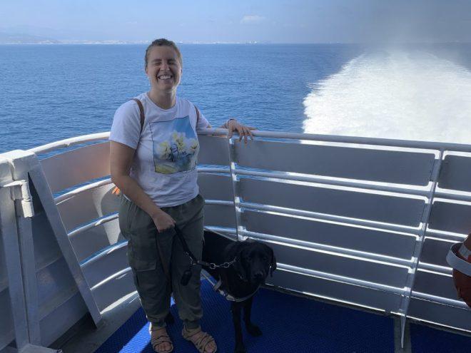 Núria en el exterior del barco sonriendo y con los ojos cerrados, y de fondo el mar con mucha espuma