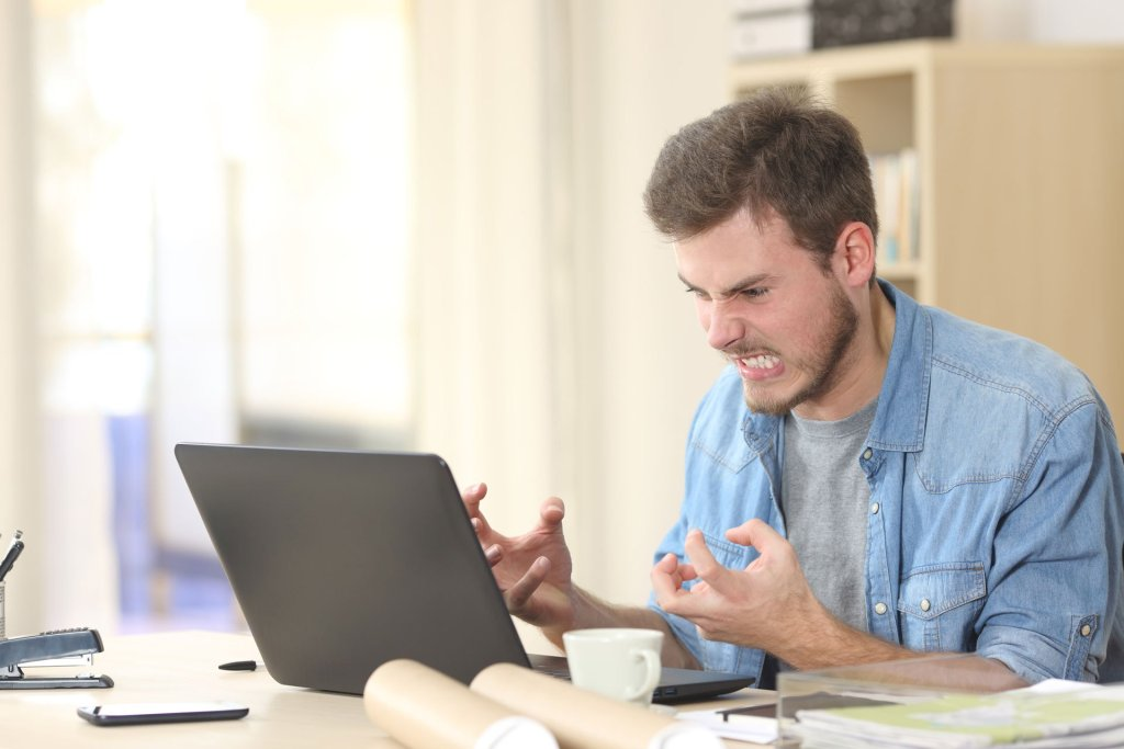 A man looks at his computer angry and frustrated.