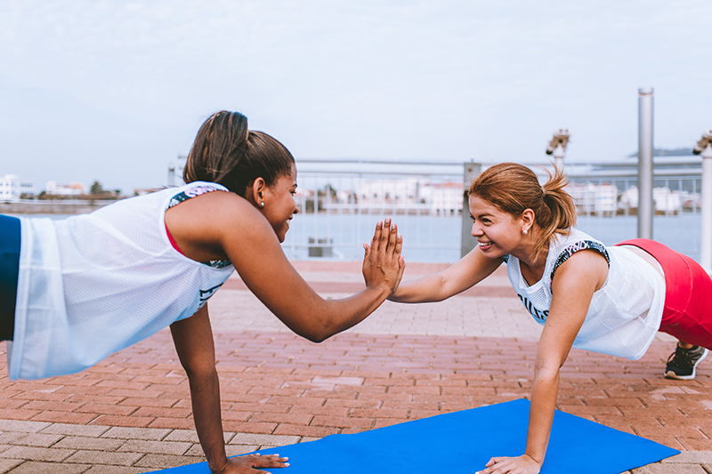 Two women doing planks together outside