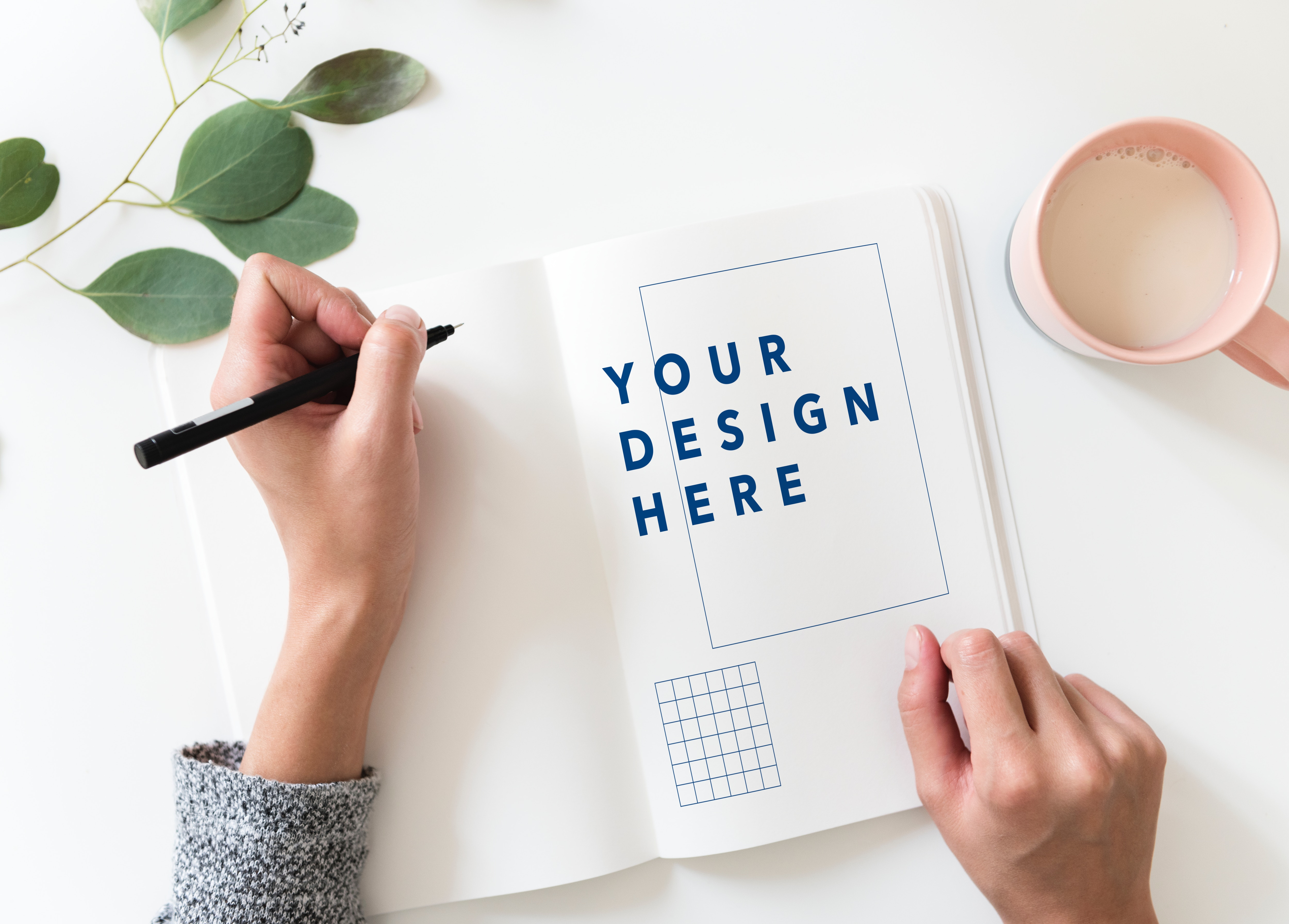 A person holds a pen over paper to begin creating a design with a template.