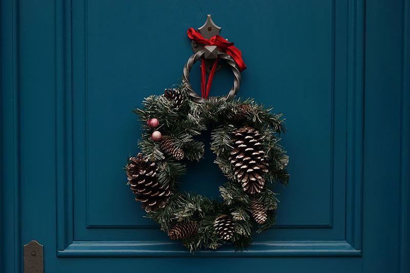 A wreath on a blue door. Around the holidays, businesses can follow these texting tips to make sure messages go out.