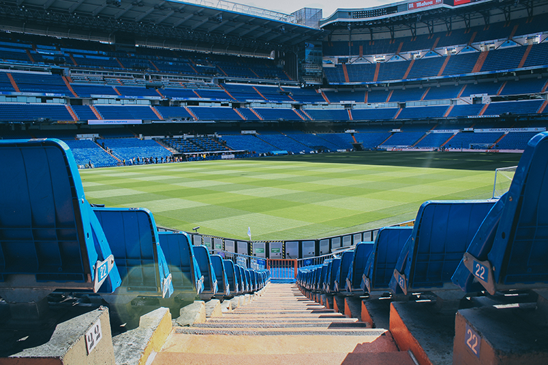 An empty soccer stadium with blue seats.