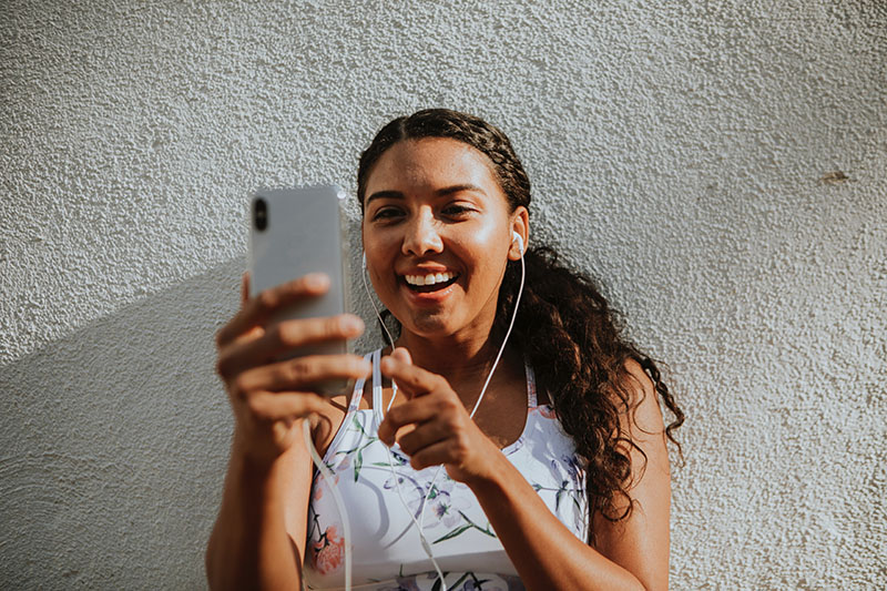 A woman with curly brown hair taking a video of herself on her phone while wearing headphones. Including videos can help you write better business texts.