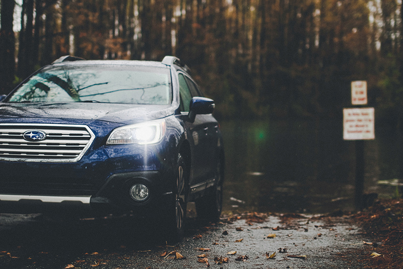 A blue Subaru on a road in a rainy area.