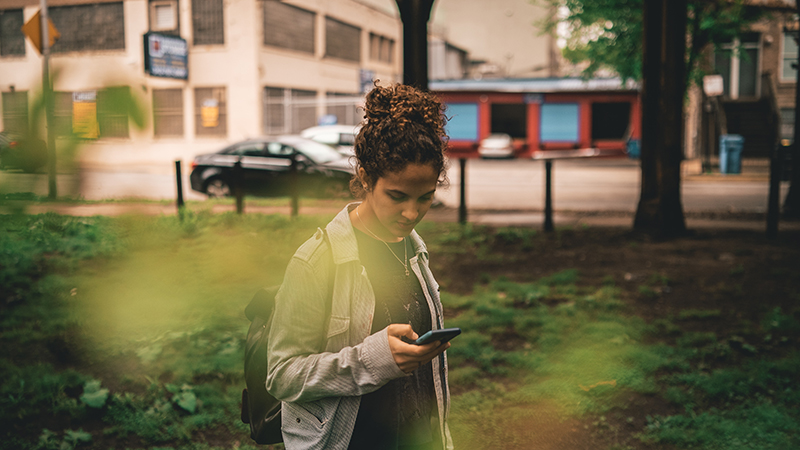 A woman looks at her phone while walking in a park.