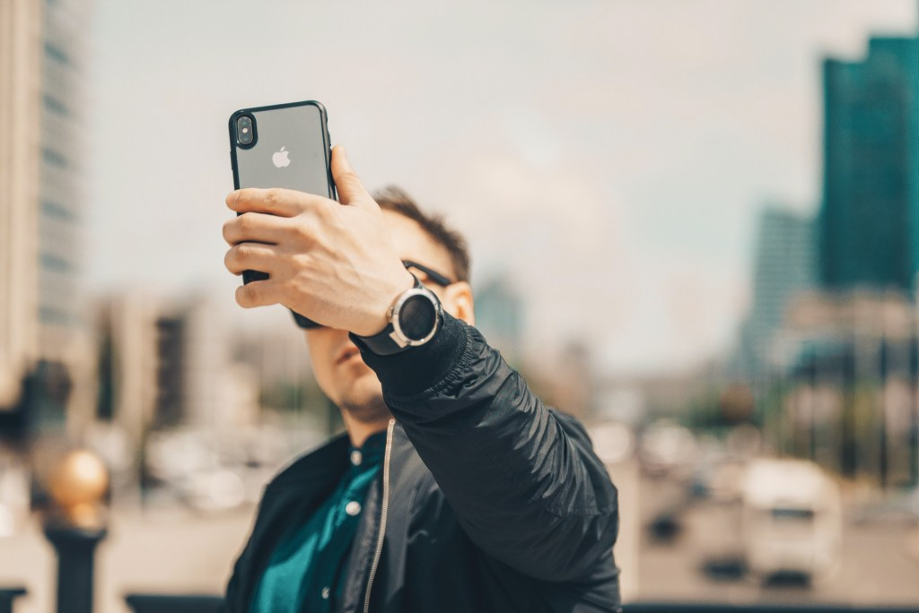 A man holding up his phone in front of his face.