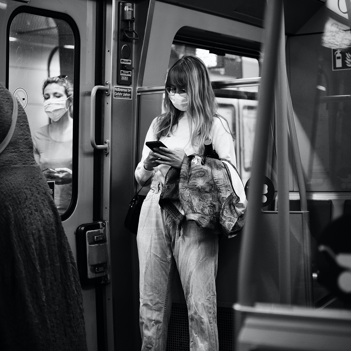 Woman with long hair, wearing a mask and texting while standing on subway car.