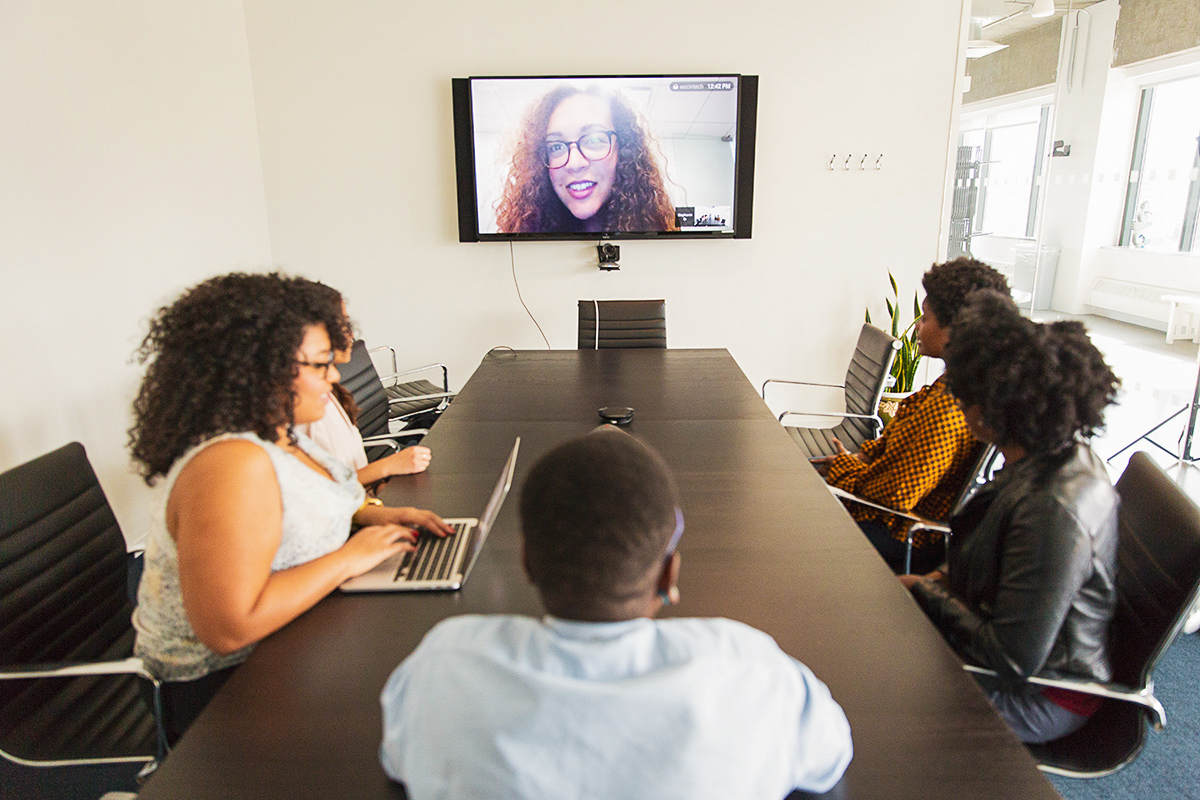 A group of 5 women sit a conference table in an office while in a virtual meeting with 1 person on a TV screen.