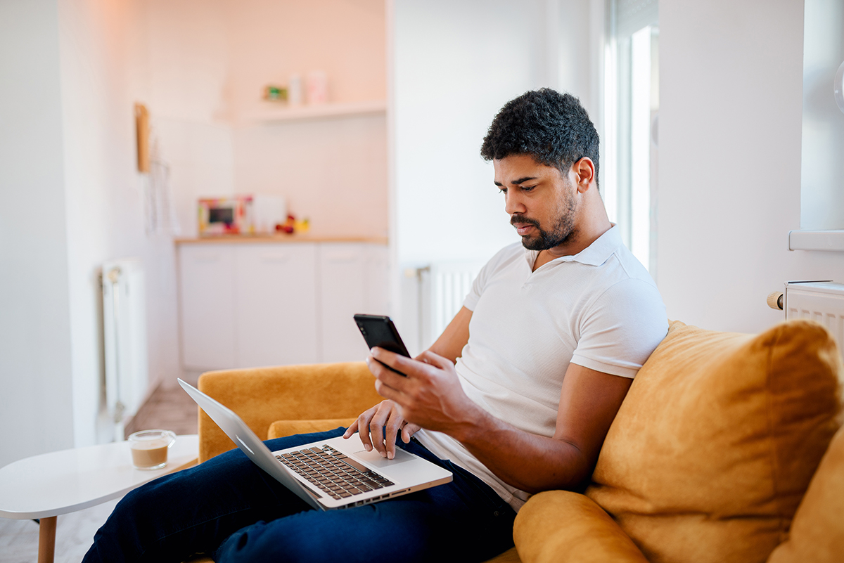 20-something man sitting on sofa with laptop in his lap and using mobile phone.