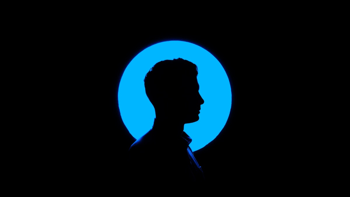 Silhouette of a person's head and shoulders in a profile view with a blue background.