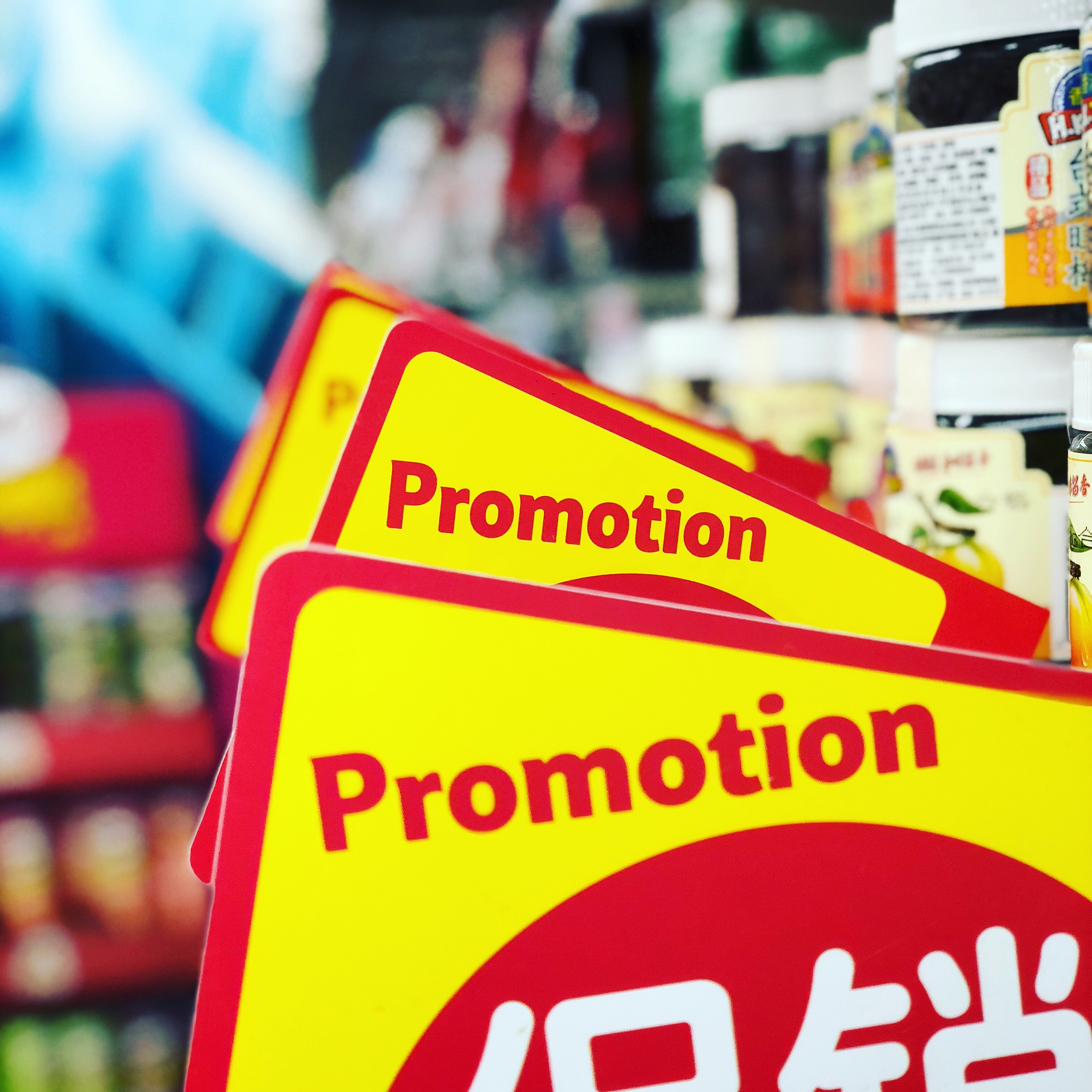 """A yellow sign with red writing that says """"promotion"""" in a store"""