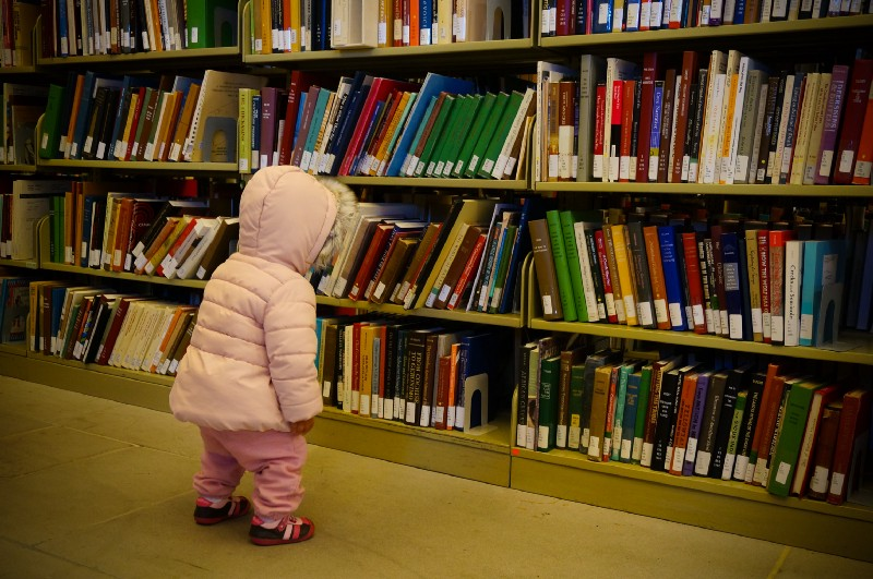 Child looking at bookshelf