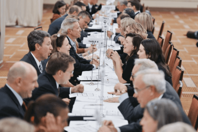 A long table with participants of a speed networking event