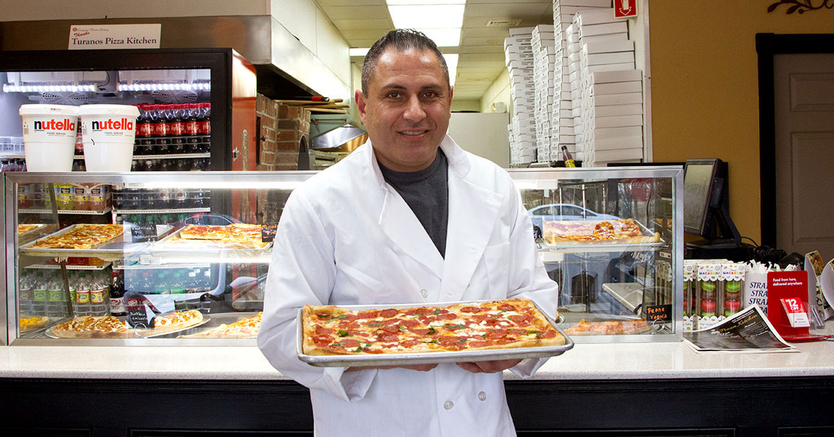 Pizza maker showing a freshly made pie