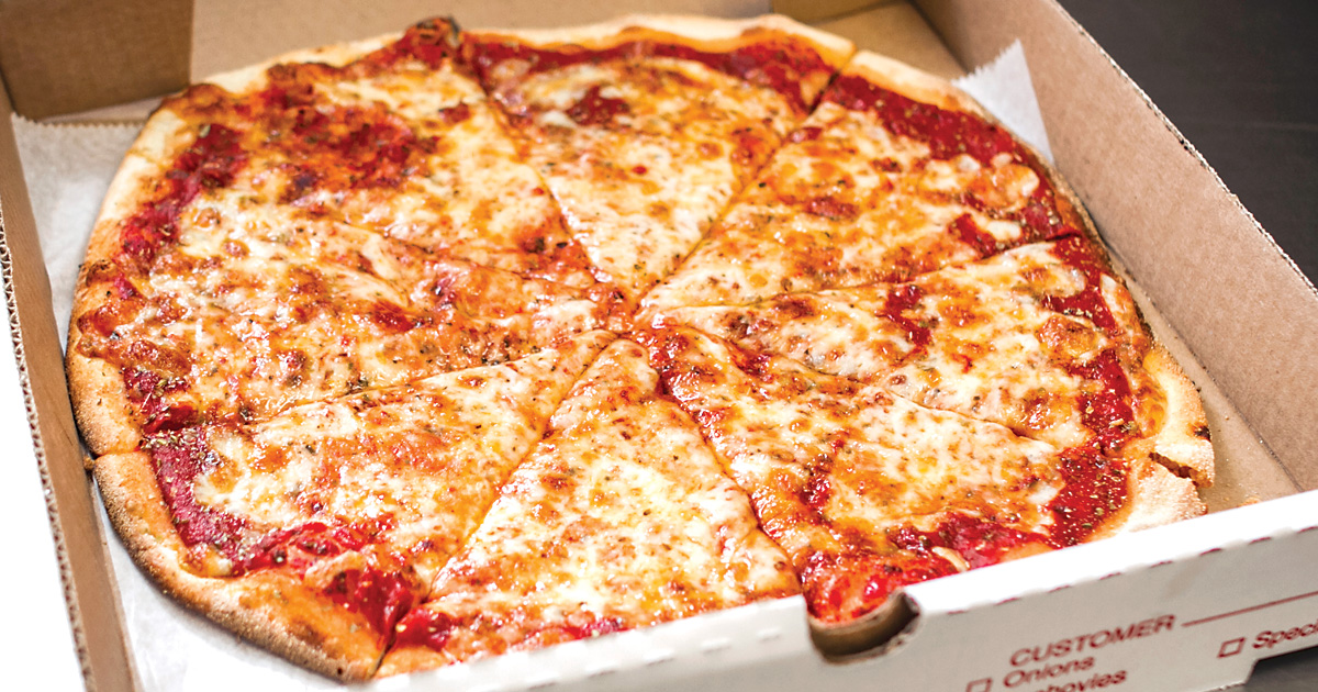 Pie of cheese pizza sliced in a box