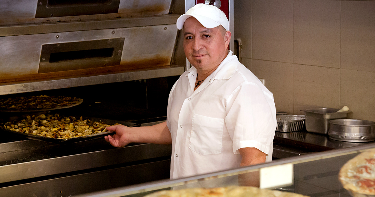 Smiling pizza maker taking fresh pizza out of the oven