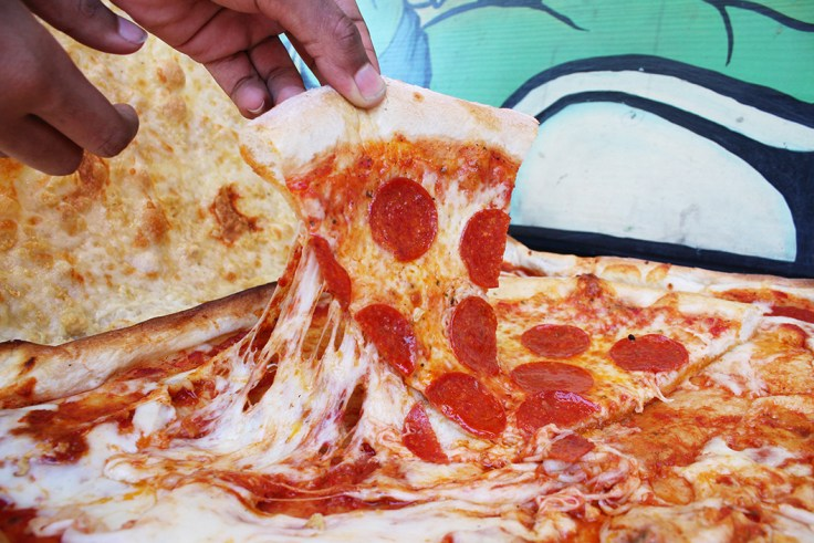 A hand pulling a pepperoni slice out o a box made of more pizza.