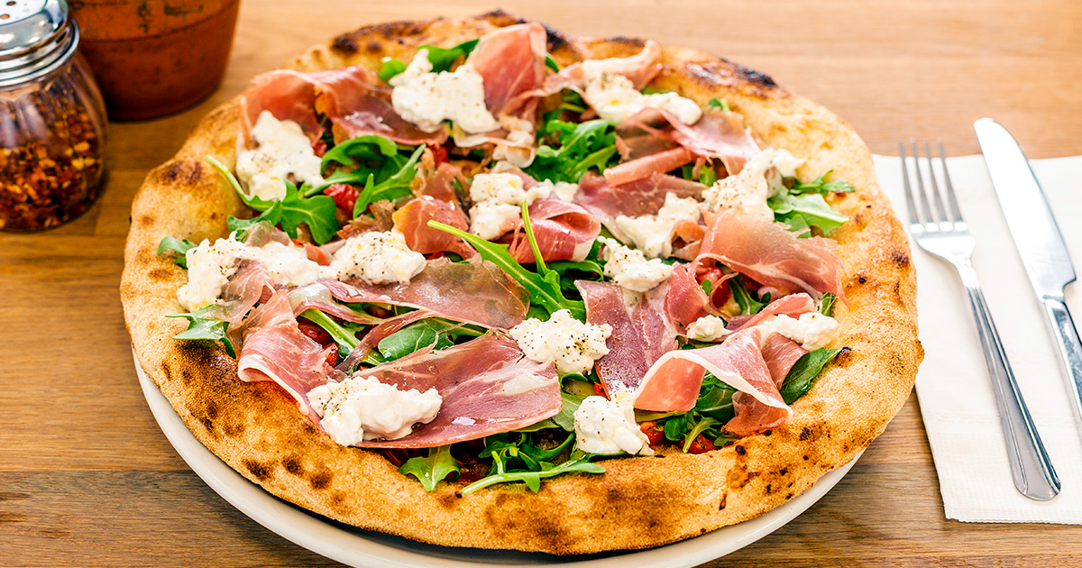 Close-up of a pizza topped with prosciutto, argula, and burrata.