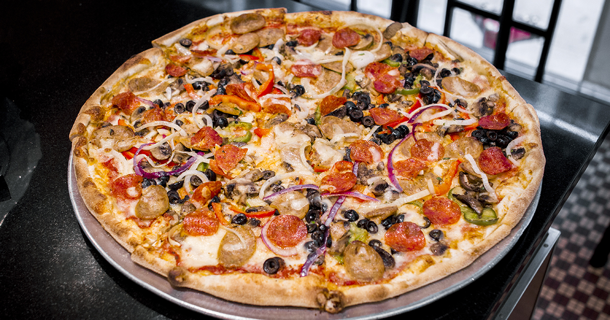 A pizza topped with olives, pepperoni, onions, and more on a table.